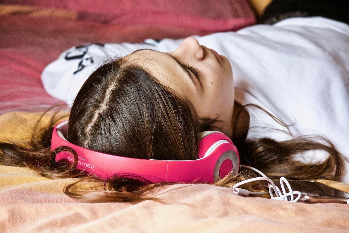 adolescente escuchando música en cama